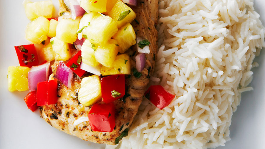 Jerk Fish with pineapple salsa piled on top of it beside a pile of coconut rice.