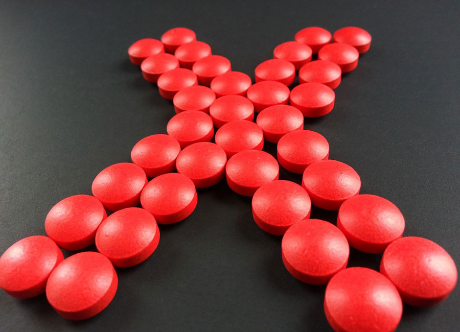 Red circular pills in a letter X formation on a black background.