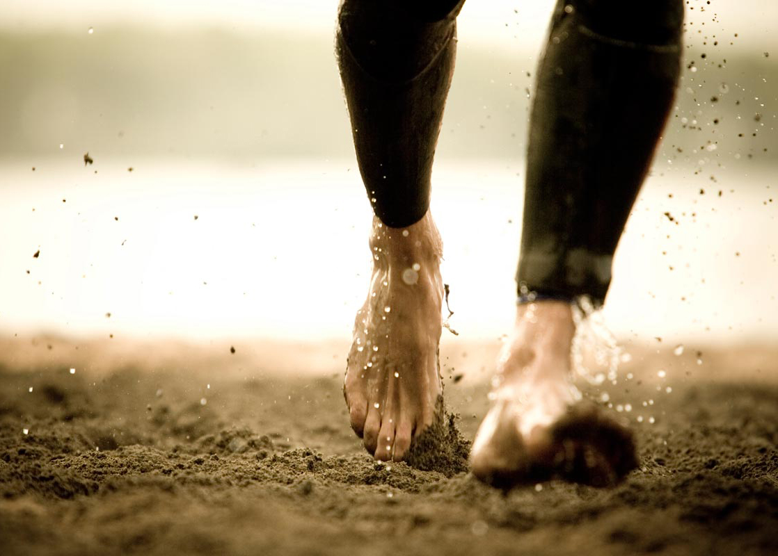 A woman walking barefooted along the beach