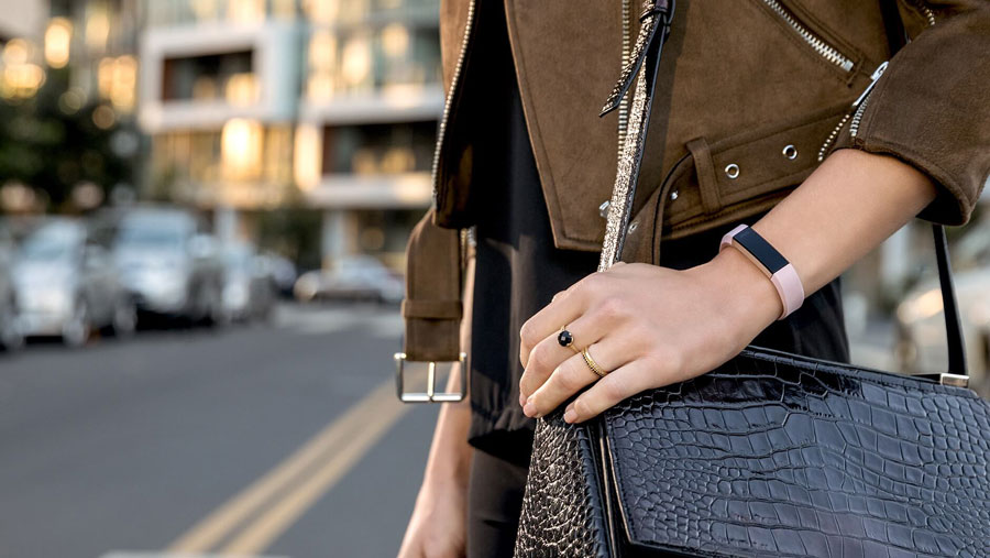 A woman crossing the street wearing a leather purse and a fitness band on her wrist.