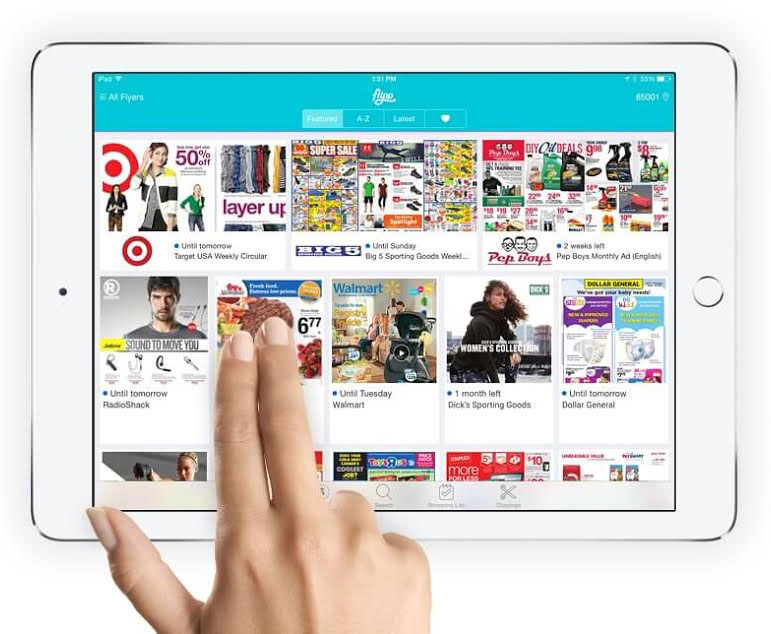 A photo of the flipp app on a tablet with two fingers touching the screen.