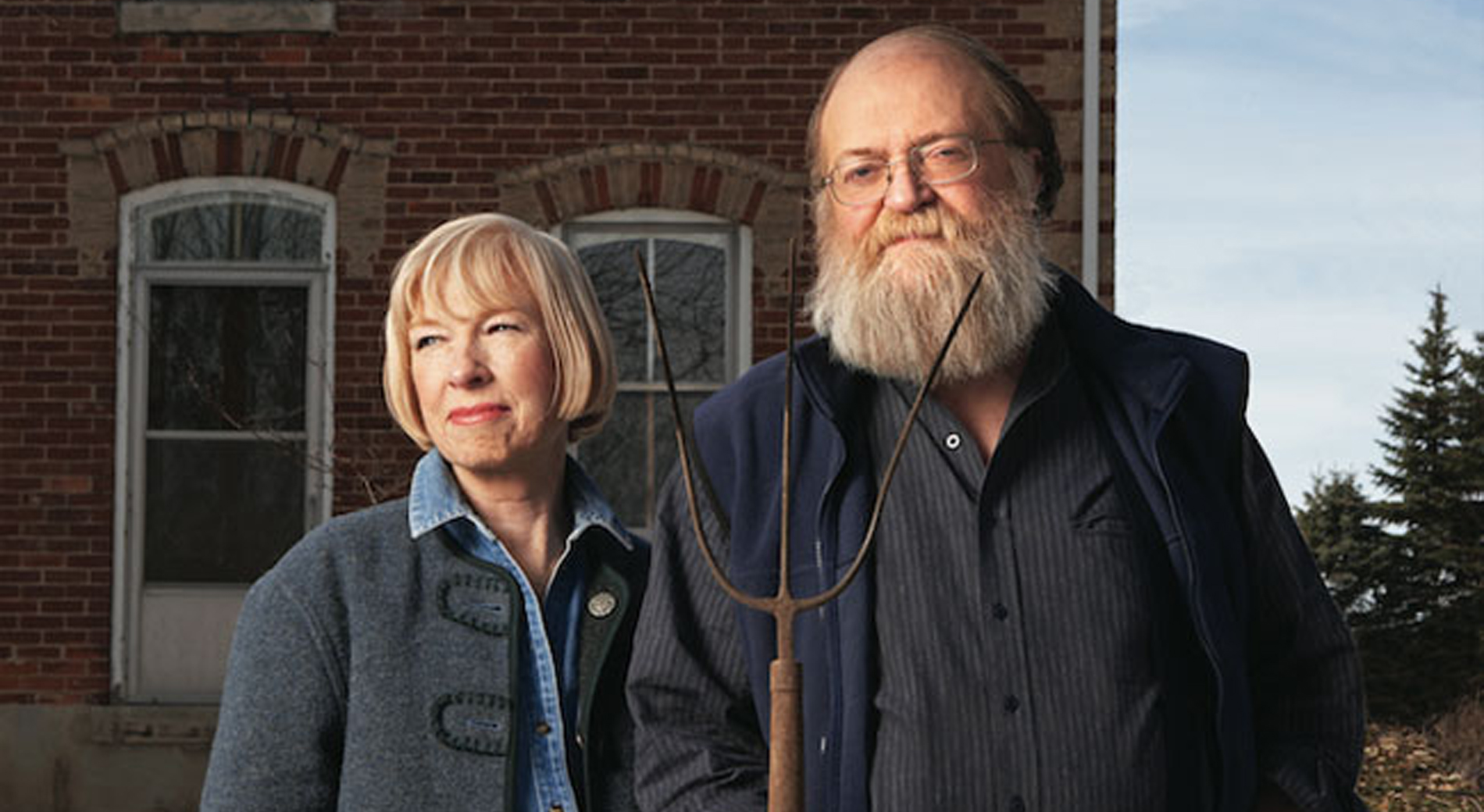 Bearded man holding a pitch fork standing beside a blonde woman.