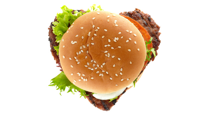 A burger with an oversized patty creating an outline of a heart shape.