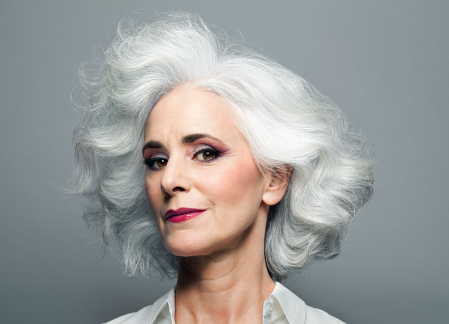 A woman with silver/grey hair wearing bright red lipstick.