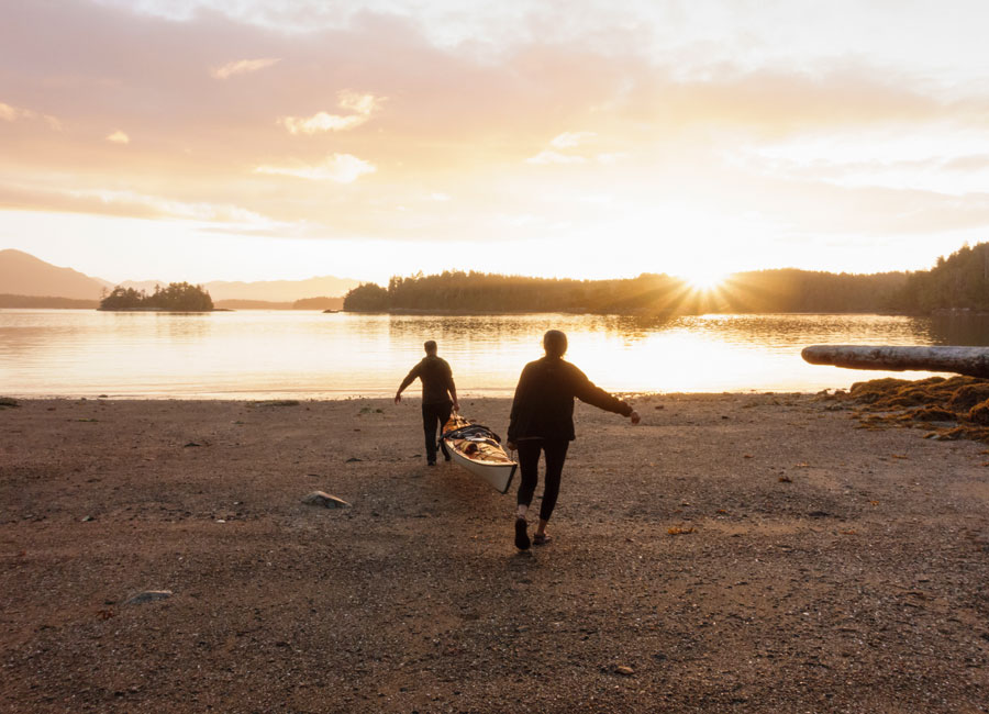 Two people carrying a canoe out to the lake as the sun rises.