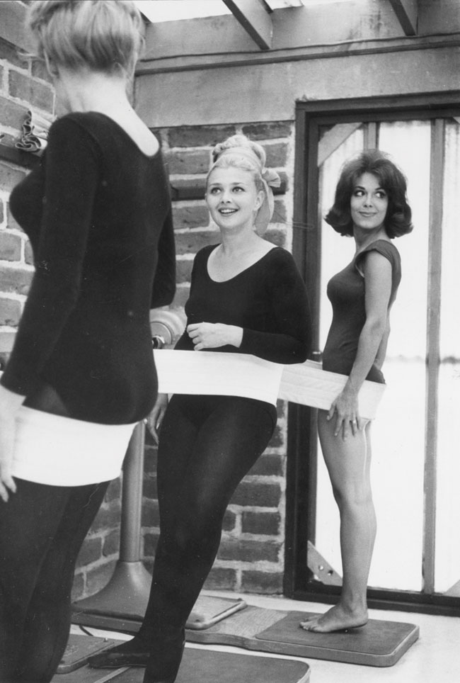 Three woman using a vibration belt, a popular weight loss device in the 1950s.