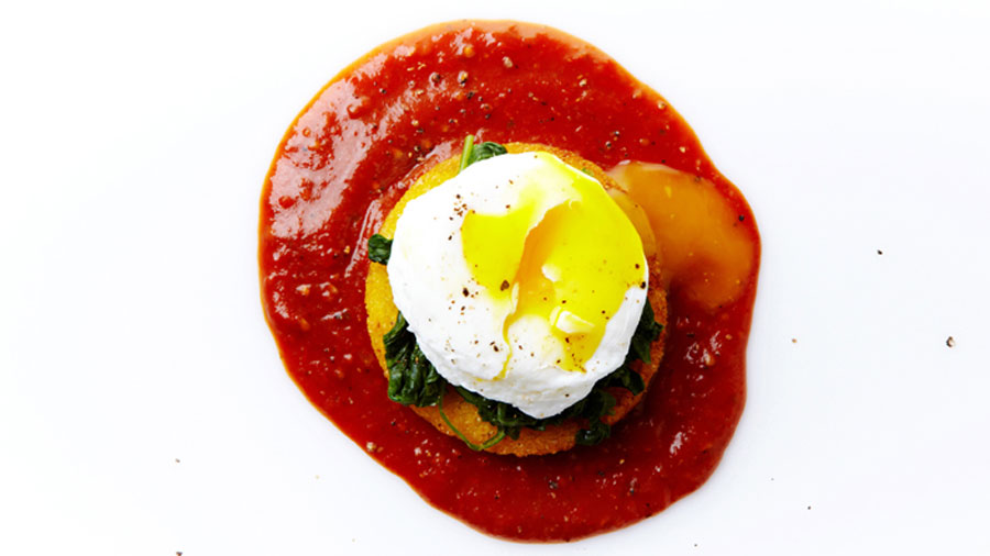 Poached eggs sitting in a puddle of tomato sauce.