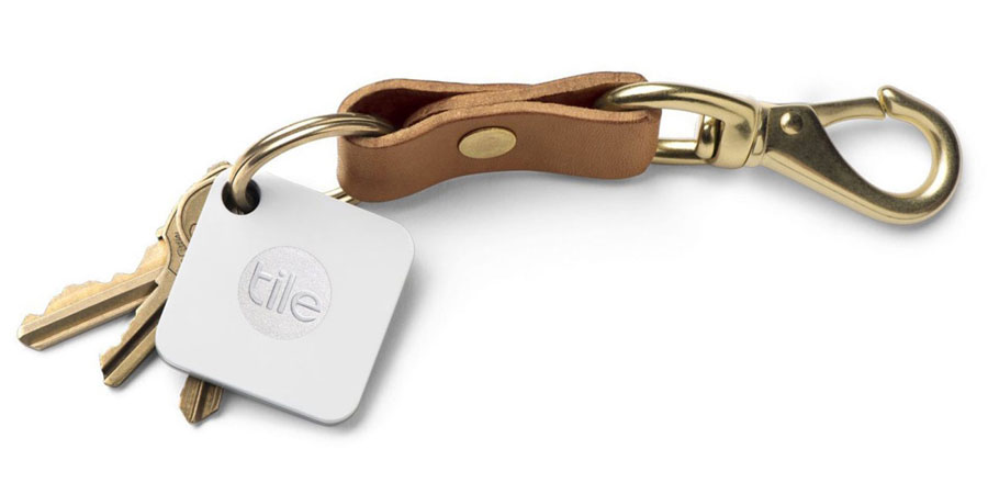 A set of keys on a leather key chain with a bluetooth tracker attached to the key ring.
