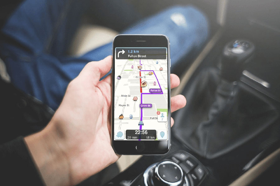 A photo of someone using the waze app with a map open on the screen displaying various icons.
