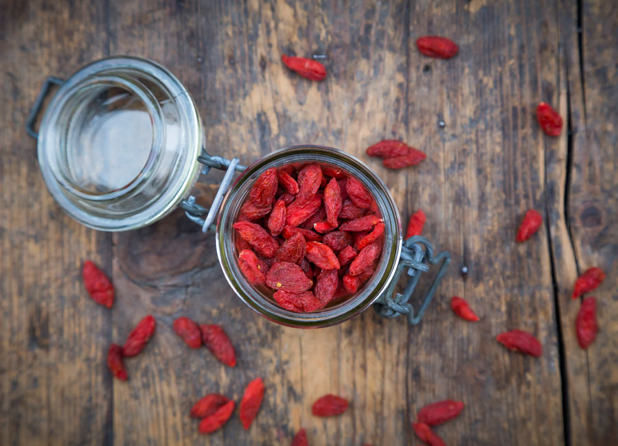 A jar of goji berries with goji berries scattered around it on a wood table.