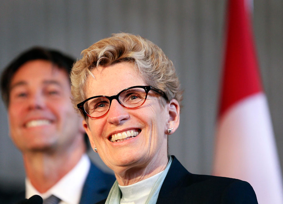 Kathleen Wynne smiles in front of a podium.