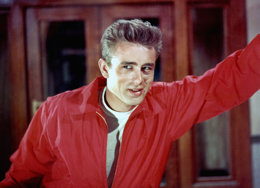 James Dean leaning against a wall wearing his iconic red jacket.