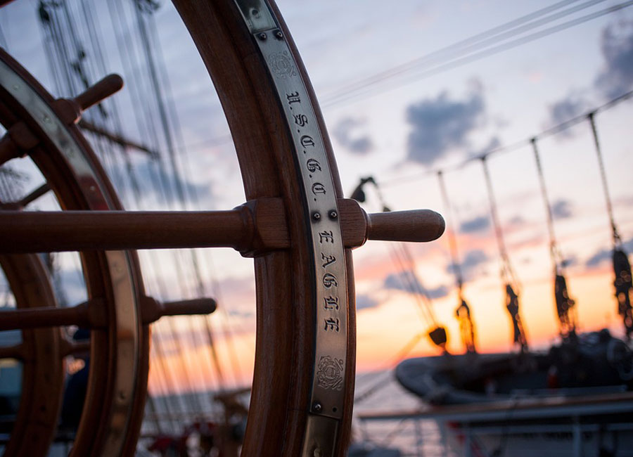 A closeup of a ship wheel with another ship and sunset in the background.