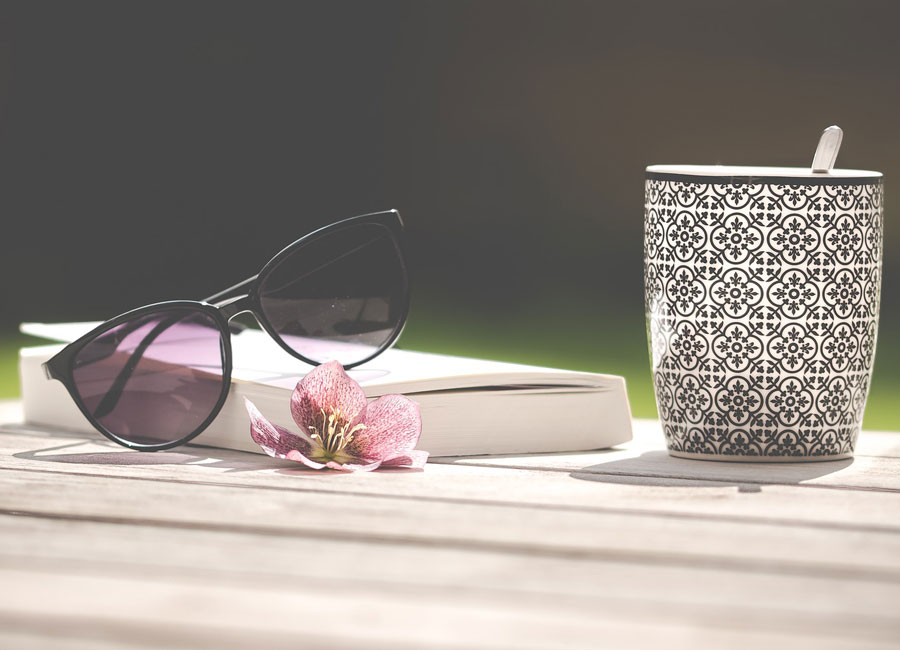 A book laying on a table with a pink flower, a mug, and a pair of sunglasses resting on top of the book.