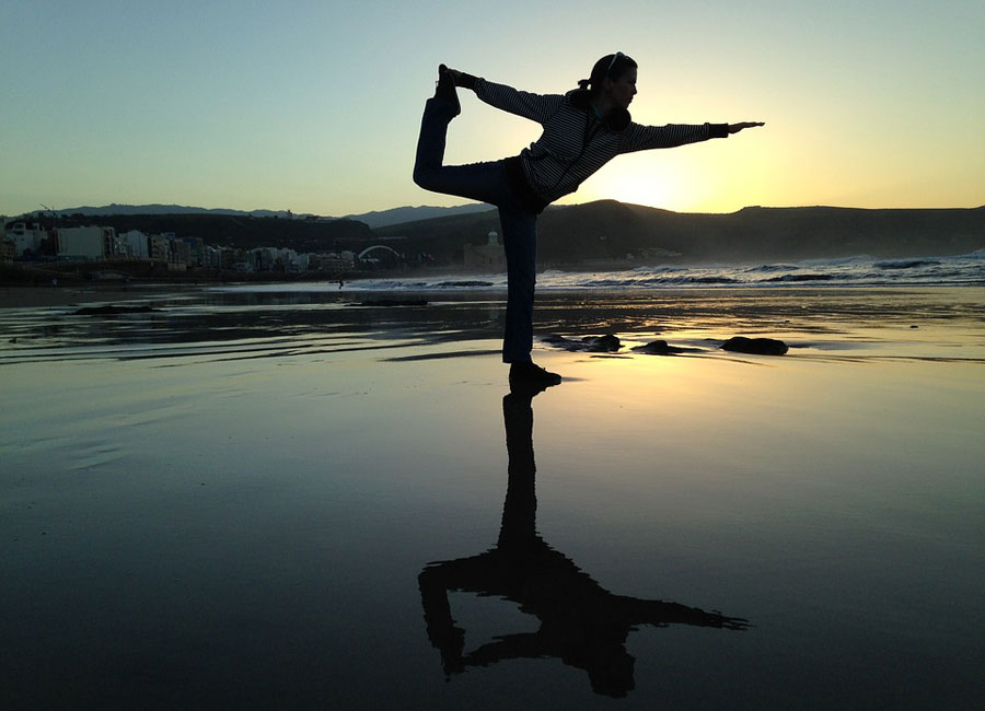 A person doing yoga with the sun setting in the background.