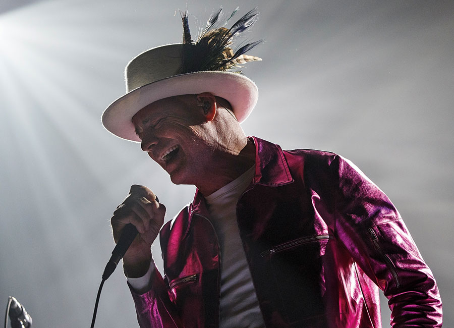 Gord Downie singing into a microphone wearing a bright purple jacket and a white hat with feathers