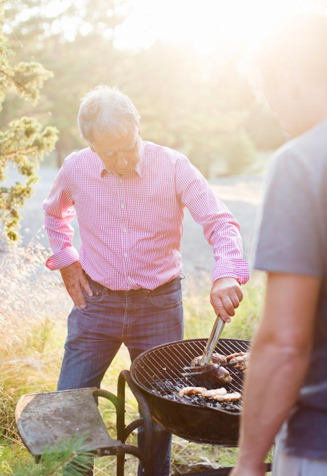 A gentleman in a pink button-down shirt and jeans attends to an outdoor barbecue