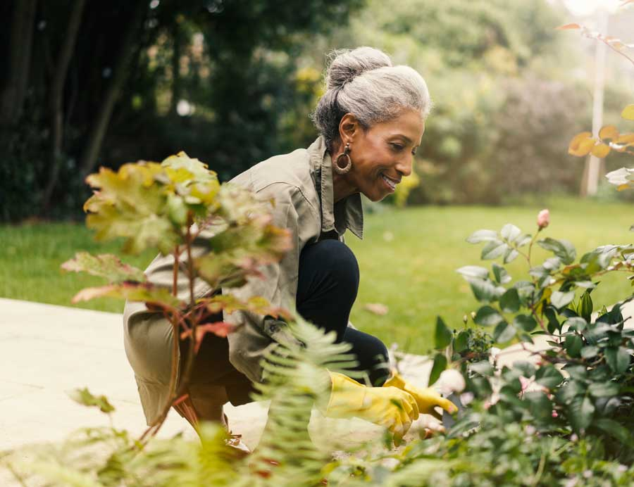 Woman kneeling down as she looks at her garden.