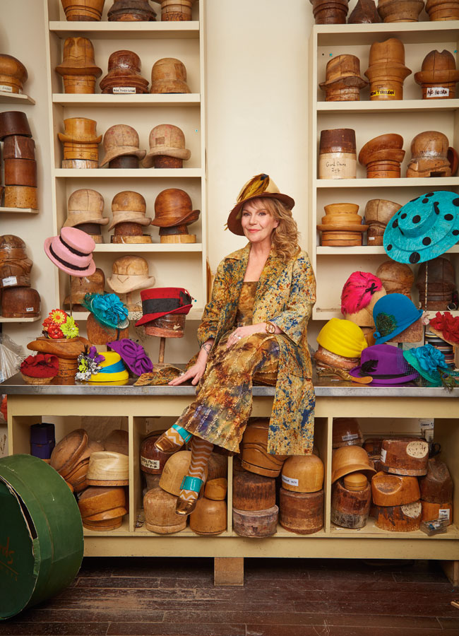 Karyn Ruiz in her shop surrounded by wooden moulds of hats and colourful hats.