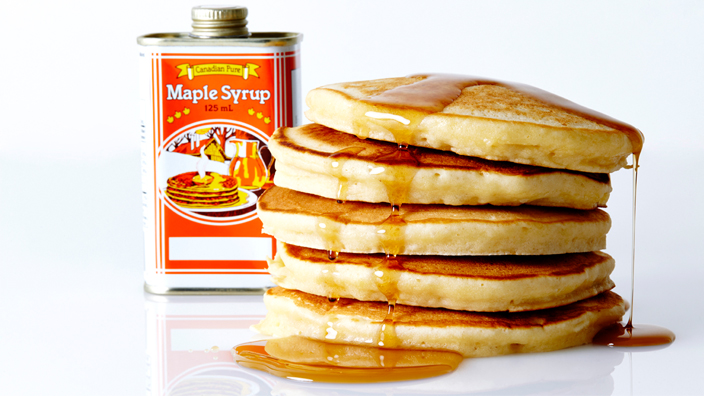 A stack of pancakes with syrup spilling over the sides.