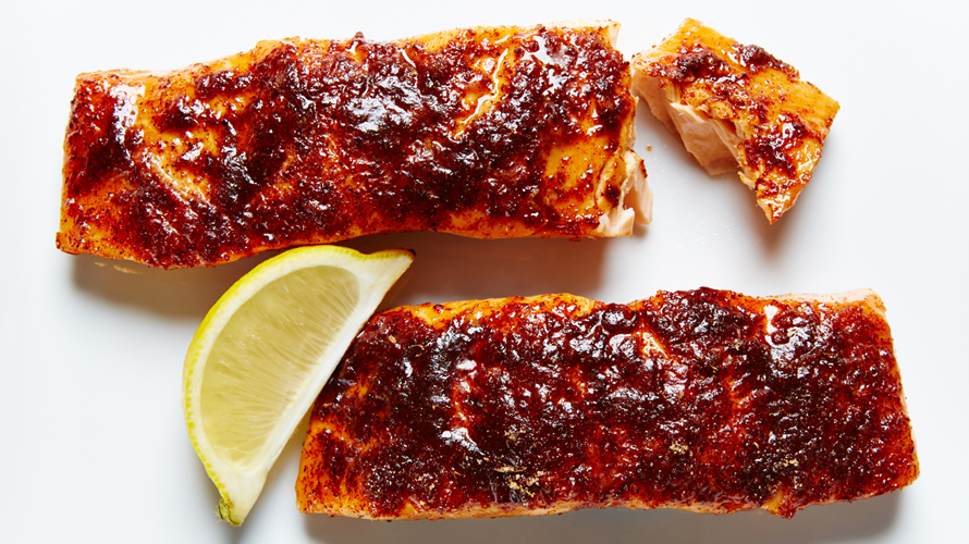 Two pieces of crispy salmon with a lemon wedge laying beside them.