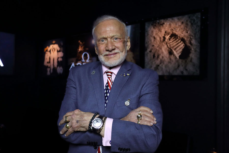 Buzz Aldrin with his arms crossed wearing a greyish blue suit.