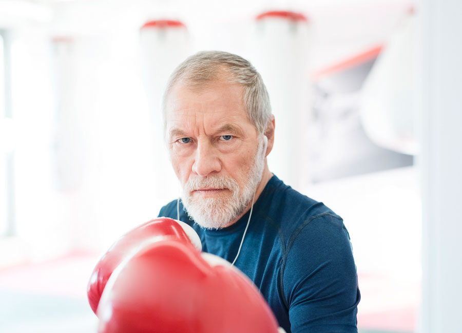 Grey haired man holding his boxing gloves up looking fierce.