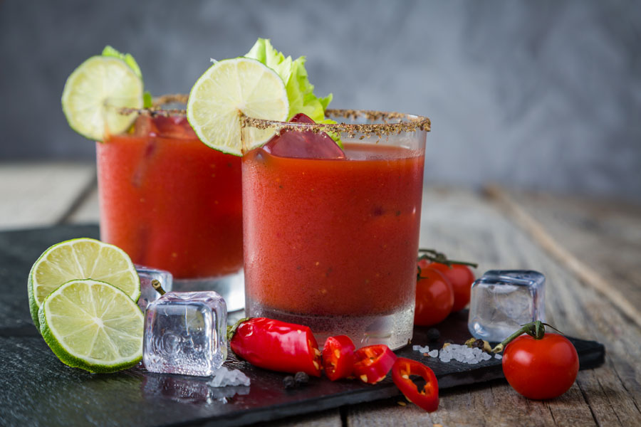 Two ice cold caesar's garnished with lime.