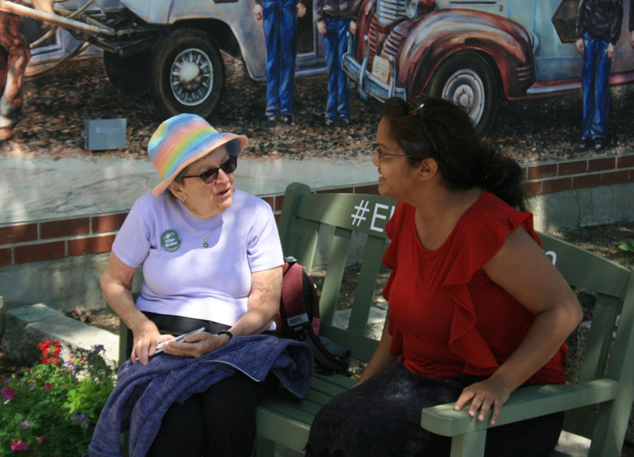 I woman sitting with an older woman on a green bench.