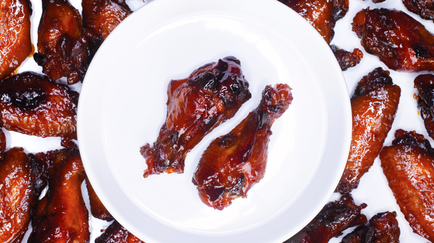 A plate with two sticky honey baked chicken wings surrounded by more chicken wings in the background.