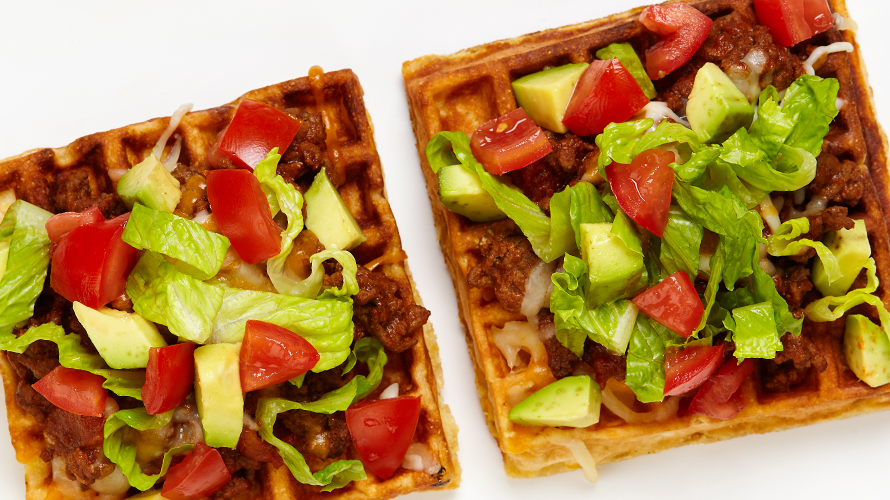 Two waffles with taco ingredients on it including ground beef, tomato and avocado.