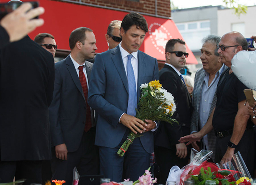 Trudeau holding flowers at a memorial for the two victims of the Danforth shooting.