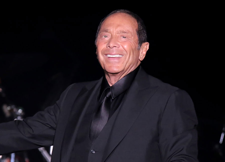 Paul Anka smiling in a black suit.