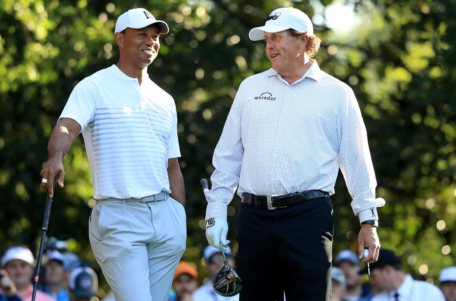 Tiger Woods and Phil Mickelson of the United States talk on the 11th hole during a practice round prior to the start of the 2018 Masters Tournament at Augusta National Golf Club on April 3, 2018 in Augusta, Georgia