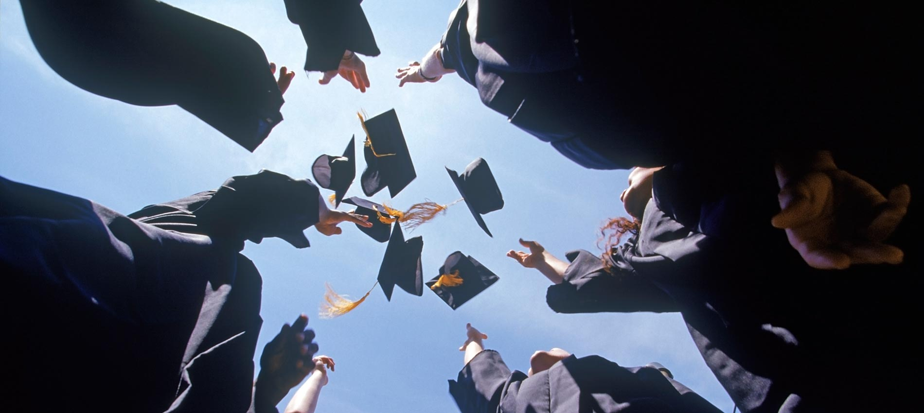 A group of graduates throwing their caps into the air.
