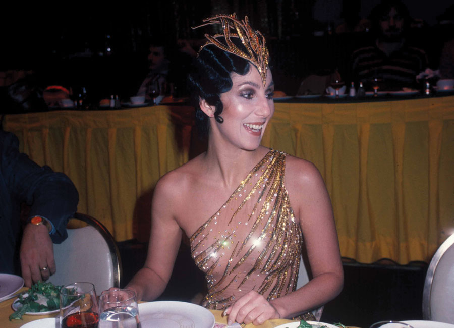 Cher wearing a gold dress and gold crown sitting at a dinner table.