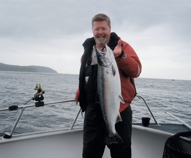 A man smiling as he holds a fish that he caught by the hook.