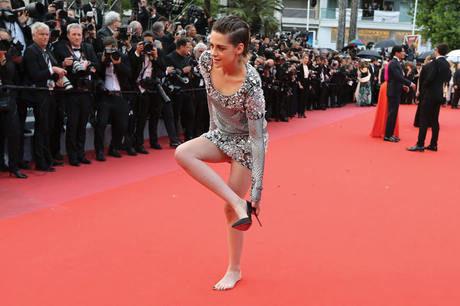 Kristen Stewart removes her shoes on the red carpet as she arrives for the screening of the film BlacKkKlansman in silent protest of the high-heels rule.