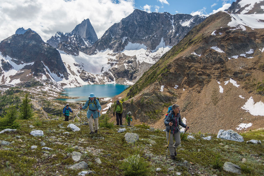 A group of people hiking a mountain. Snow covered mountains and bright blue water can be seen ahead.