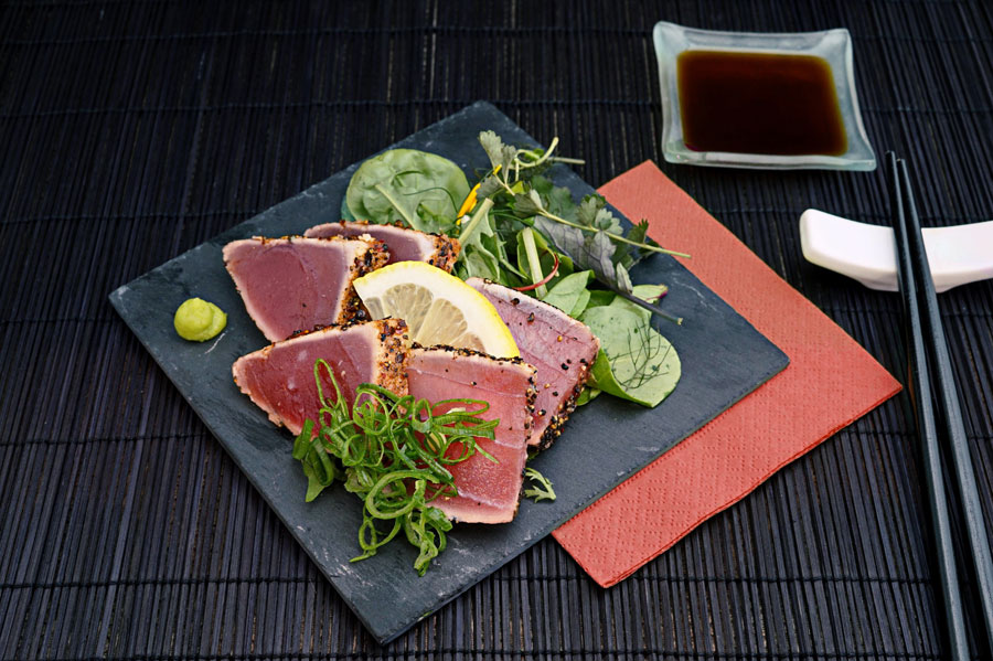 Seared tuna with greens a lemon and a dot of wasabi sauce beside it.
