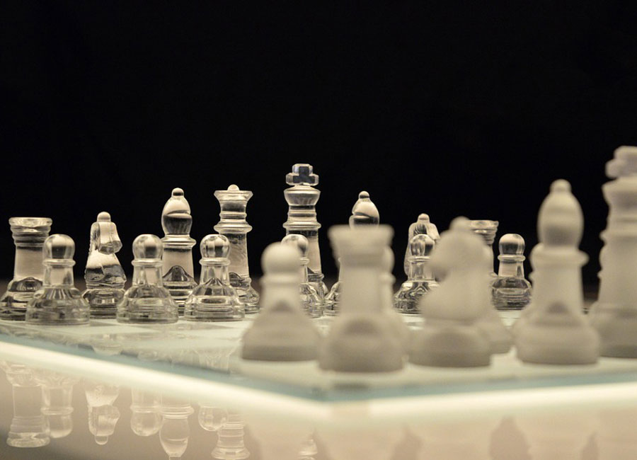 A glass chess board with smoked glass pieces on one side and clear glass on the other.