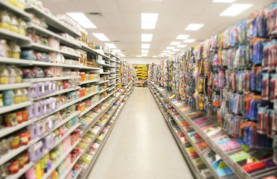 A look down the aisle of a dollar store with the florescent lights shining above.