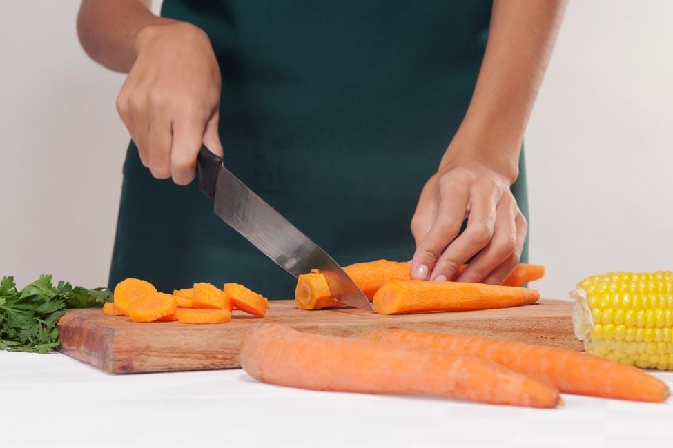 A woman slicing carrots