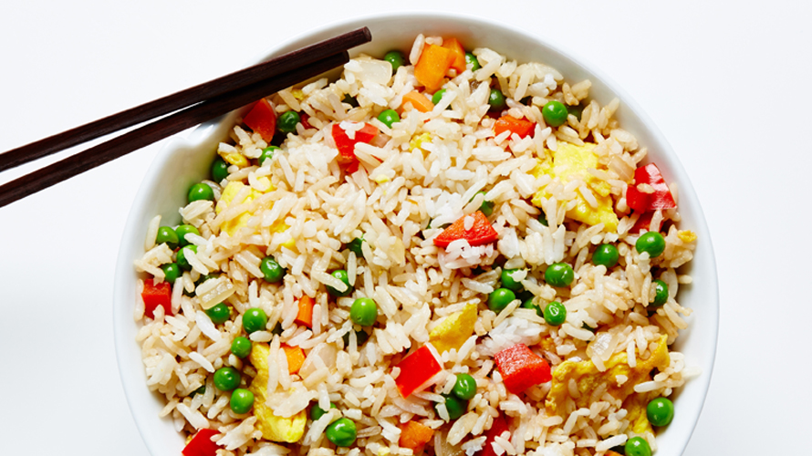 Vegetable fried rice recipe with a pair of black chopsticks sticking out.