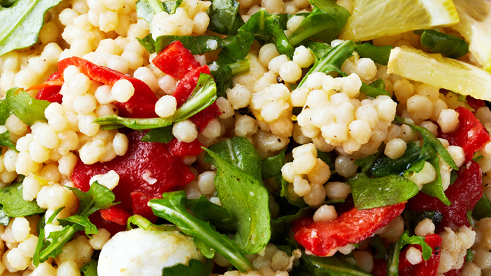 A close up of Couscous salad with tomato and greens.