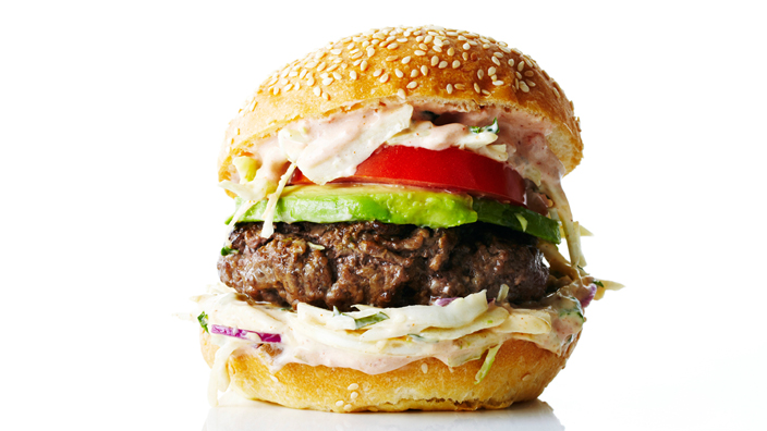 A chipotle burger with coleslaw, tomato and avocado.