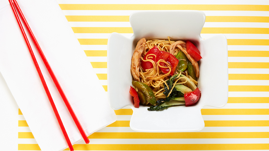 Chicken and vegetable lo mein in a Chinese takeout box with a pair of red chopsticks laying beside it.