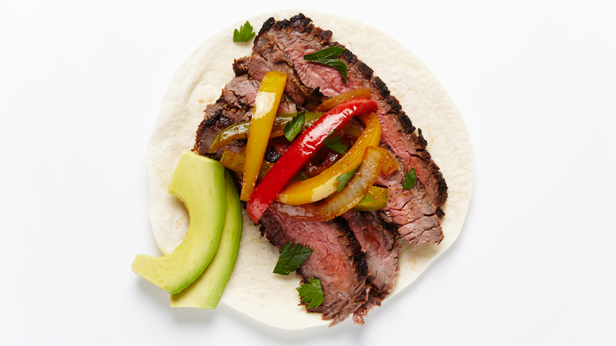 Grilled flank steak on a fajita with red and yellow peppers and avocado.
