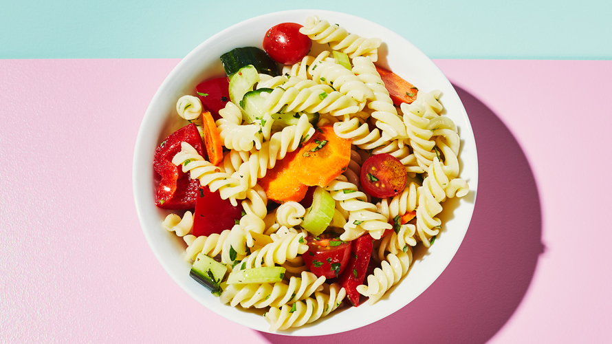 A bowl of pasta salad with peppers and baby tomatoes.