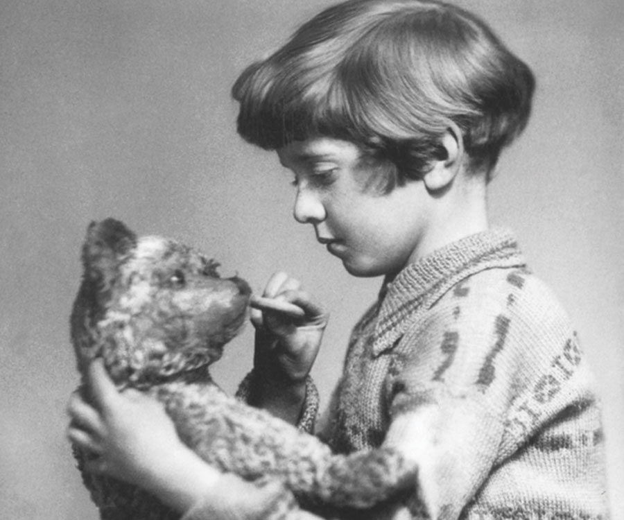 The real Christopher Robin holding his stuffed bear.